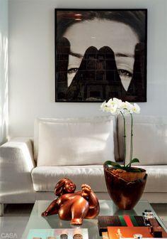Na mesa de centro, escultura de gordinha de Eliana Kertész. Sofás e poltrona Diz, de Sergio Rodrigues, da Toque da Casa. As fotos nas paredes do apartamento são assinadas por Cristiano.