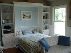 Murphy bed idea. A custom full size bed built in. That is flanked with matching white wood shelves. With pale turquoise walls.