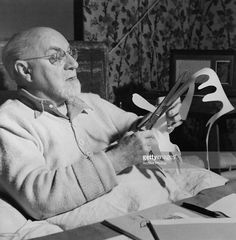 French artist Henri Matisse making paper cutouts in bed at his home in Vence, France, circa 1947.