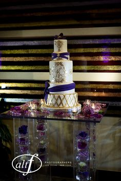 Plexi glass cake table with white dahlias, purple vanda orchids, purple lisianthus, and lavender roses floating in their own vases stacked on top of each other in legs #naakitifloral