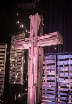 Pat Miller, Brandon Stephens, and the Stage and Lighting Team fromFaithbridge ChurchinSpring, TX built a new stage backdrop for the fall and Christmas season. They used some donated wood pallets, a variety of Vintage Edison bulbs, some lumber theyhad on hand, and a re-purposed cross from a previous backdrop. Theybuilt six pallet columns of varying heights with 2 x 4's and two donated pallets for each one and then suspended several vintage light bulbs in front of them. Then theycut two…