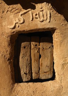 """""""Allahu Akbar"""" protects the window on the outside and a Wooden shutter on the inside of  a Ghurfa in Nalut, Libya"""