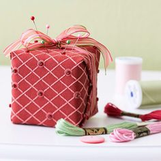 This pretty-as-a-package pincushion is the perfect gift for a crafty friend. Cover a foam square with fabric (wrap it like a gift) and secure along the edges with fabrics glue. Glue on beads and tie on a ribbon bow.