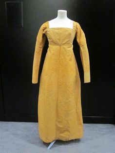 1800-1810 dress made of silk and wool poplin lined with linen and cotton. With the dark-yellow color, long sleeves and robust fabric, I'm guessing this one was worn during the colder months.