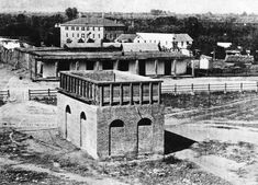 A far cry from the Olvera Street we know today, this shot of the plaza from 1860 shows one of LA's first water reservoirs--the brick structure shown in the center of the Plaza. The adobe directly behind was owned by Augustin Olvera. The 3-story building was the Sisters of Charity Hospital.