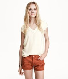 V-neck blouse in woven satin fabric. Short sleeves, hemstitch embroidery at top, and rounded hem.