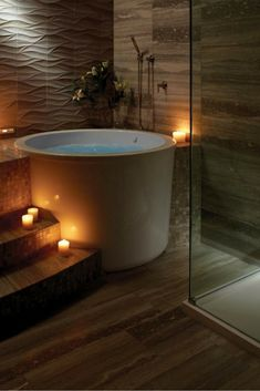 Japanese design lends itself well to the bathroom, because it has an evident focus on tranquility and a sense of peace. [Japanese Style Soaking Tub, Japanese Bathroom Design, Japanese Spa Ideas, Japanese Soaking Tubs, Textured Tile Wall, Glass Shower Doors, Tile Bathroom Floor, Bathroom Ideas]