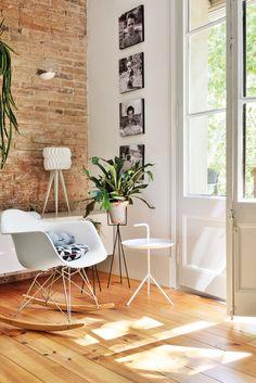 Busca el pasado. Como esta pared en la que la decoradora Neus Casanova dejó el ladrillo visto. Balancín, modelo Rocking Chair, de Charles y Ray Eames, y mesa auxiliar, de Ottoyanna.