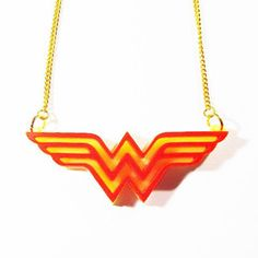 Wonderful Wonder Woman insignia pendant, fashioned from double layer laser-cut acrylic. On your choice of approximately 41cm gold or silver plated split curb chain,or black leather thong. Measures approximately 65mm x 25mm. Nickel and lead free.