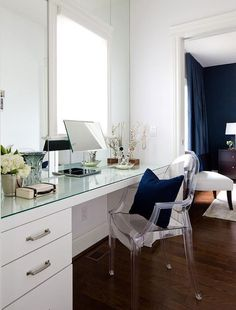 Chic dressing room features a full length glass top dressing table paired with a Kartell Ghost Chair placed under a window.