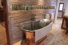 Freistehende Badewanne aus Messing in Altholz eingefasst. Sie ist Teil eines Badezimmers in einem bayerischen Landhaus. Gefällt sie Dir?