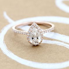 The gorgeous (and ethical) Heroine Accented Engagement Ring pictured here in Rose Gold with a Pear Cut Diamond Hybrid® center stone.