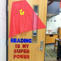 Reading is my super power- I cut red plastic table cloth into the shape of a cape and taped on the symbol. Middle school library display