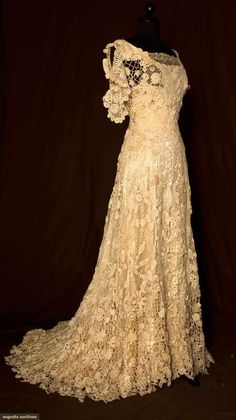 """Irish Crochet Trained Gown Circa 1908 in Cap sleeve, low rounded neckline front & back, fitted through high waist, very full trained skirt, small, large & 3 dimensional crochet flowers & foliage, cream satin built in boned lining, waist tape stamped """"TRAVERS, 106 E. 58TH ST, NY""""."""