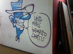 """Grafite realizado na parede lateral da gráfica da FAU, no qual se lê """"Leia mais barato grátis"""". É provável que a intervenção tenha sido realizada por algum aluno da FAU, sendo destinada aos demais pessoas que transitam pelo prédio."""