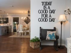 A custom black metal sign with a positive message greets guests in this entry space. A small black wood bench and floor lamp provide a cozy sitting area before entering the adjacent dining room and kitchen.