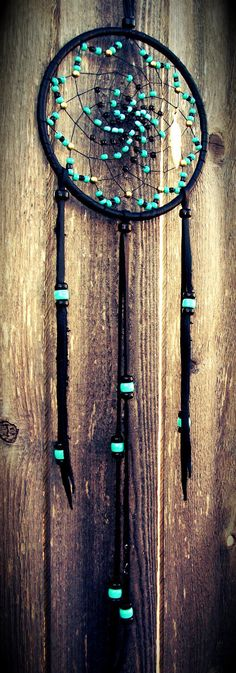 Dream catchers are usually colorful and made with feathers. But a black one with only beads to design it would totally work both as a dream catcher and a modern-decor.