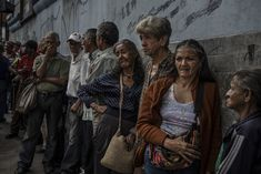 """Los Teques, Venezuela, 22 September 2017. Ama Heredia, 53, (centre in blue blouse), and Zoraida Morales, 66, (third from right) arrived at 6am to wait in line for several hours to receive a free bowl of soup for lunch from a soup kitchen run by the Iglesia Nuestra Señora del Carmen """"Luis Igartua"""" Catholic church in Los Teques, Venezuela. The women said they come regularly because even though they each work, they can no longer afford food because of widespread shortages and soaring food…"""