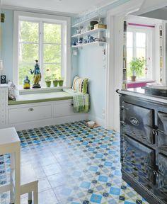 Det lilla köket rymmer ingen matplats men har en inbyggd bänk vid fönstret. En krishnastatys färger och mormors korkmatta blev utgångspunkt för golvet från Centro kakel. Foto: Mikael Dubois