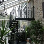 The extra height in this monopitch conservatory allows access to the first floor by this spiral staircase