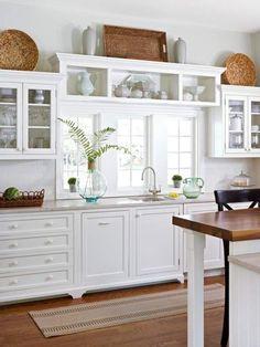 biała kuchnia rustykalna z wiklinowymi dodatkami i wyspą kuchenną z drewnianym blatem