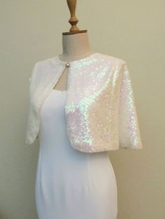 The ivory sequin bolero is the perfect cold weather accessory for a fall or winter wedding.It is lined with ivory satin lining. Very elegant and