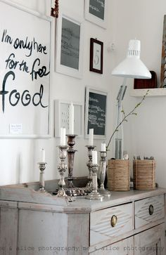 Words on the walls (framed!) What an ideal! Also, I like the barebones furniture? Like, the rustic kind of... weather washed wood. Beautiful. White walls really brings in the light. Not a fan of those candlesticks, but I love the words on the walls!