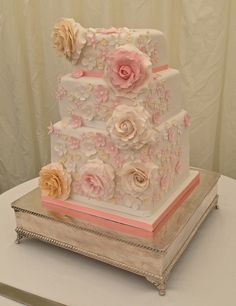 A modern square wedding cake with soft pick roses.