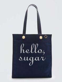 Stay sweet with our Hello, Sugar Tote—a cheerful style statement you'll reach for daily. Offer friendly Hello Sugar Southern greetings everywhere you go with a roomy carryall featuring our contrasting pinstriped lining and our signature magnolia-shaped hardware. Personalize your tote by hanging our custom Key Fobs from the attached exterior ring.