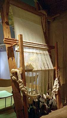Replica Norse loom with stone weights creating tension on warp threads.