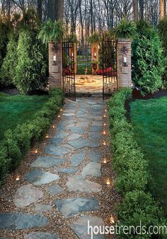 Boxwoods line a path to a gate which leads to a lovely sitting area