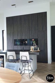 Deze oud bruine eiken hoge kastenwand is geheel op maat gemaakt en afgewerkt met geheel zwarte Bosch inbouwapparaten.