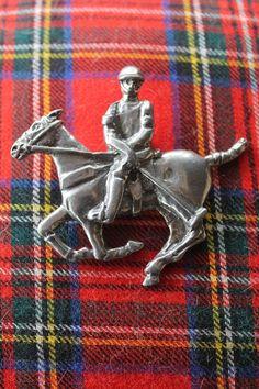 Silver polo pin on tartan