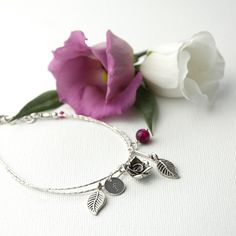 A beautiful handmade sterling silver English Rose Charm bracelet. With 5 different charms including a rose, two leaves, a semi precious gem stone and a personalised initial charm. Choose between an Indian Rose or a Rose Quartz gem stone. This is the ultimate gift to tell someone how much you love them. Personalise for your loved one on their wedding day, for your mum on Mother's Day or for your best friend's birthday. The bracelet measures 20cm.