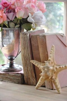 Pink roses in a vintage silver trophy, antique books and a single starfish make a lovely vignette. Cottages By The Sea, Beach Cottages, Old Books, Vintage Books, Antique Books, Vintage Journals, Coastal Style, Coastal Decor, Coastal Living