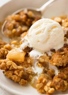 Close up of Apple Crumble in a rustic white bowl with a scoop of vanilla ice cream, ready to be eaten. Best Crumble I've made to date!