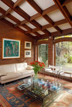 The carpeted living room looks rustic with coffered wooden ceiling exposed brick wall extending to the arched opening. Photo by Carolina Katz + Paula Nuñez Red Brick Walls, Exposed Brick Walls, Living Room Designs, Living Room Decor, Living Rooms, Brick Architecture, Elegant Living Room, Modern Living, Window Design