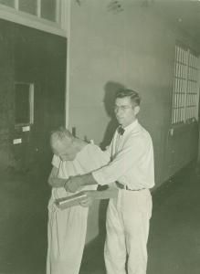 Orderly, Eric Kindy assisting patient to bed. New Jersey State Hospital, Marlboro, NJ (1945)