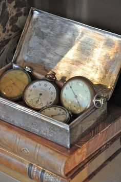 old pocket watches in vintage tin box on top of old books