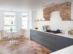 Tomettes hexagonales avec façade de cuisine grise murs blancs table ronde blanche