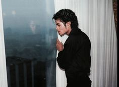Michael Jackson... I like the contrast between (what appears to be) the flash and Michael's clothes, the contrast between his clothes and the curtains, and the contrast between the curtains and the dark gray, rainy day on the other side of the window. The way the flash hits his face and the way his face's reflection acts as a flash of light on the window, over the gray skies is also interesting.