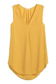 Blusa de mangas cavas: Blusa de mangas cavas e corte largo em tecido delicado. Tem decote em V com debrum em cetim, prega na frente, macho na parte de trás do pescoço e base arredondada. Ligeiramente mais comprida atrás.