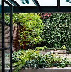 Costumamos ter a impressão de que um jardim exuberante precisa de muitas flores e cores, não é? É claro que espécies floridas são lindas, mas um paisagismo monocromático e feito só com folhagens também pode ser incrível. A prova está no projeto abaixo, realizado pelo escritório Rees Roberts + Partners, de Nova York. (Quem reconhece a foto do nosso Instagram?).  A construção é uma típica townhouse nova-iorquina, então são três andares e mais uma cobertura – que também ganhou um terraço com…
