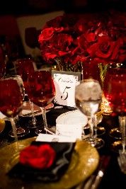 red and black tablescape with red glassware, red flower centerpiece, black napkins, and gold plates