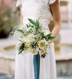 Dreamers and Lovers wedding dress with a white + green bouquet