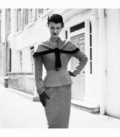 A woman modelling a tailored suit by Simon Massey with a short cape and a nipped waistline, 1954