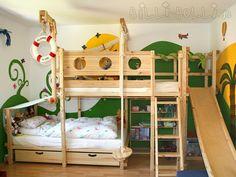Mit dem Etagenbett-seitlich-versetzt von Billi-Bolli wurde die volle Breite dieses Kinderzimmers ideal genutzt: Ein Kind schläft über dem anderen und für eine Spielhöhle unter dem Bett ist auch noch Platz. Je nach Lust und Laune sorgen mal die schöne Wandbemalung der Eltern und das Kletterseil für Dschungelfeeling, mal wird das Bett dank Kojenbretter und Steuerrad zum Schiff auf hoher See. Bettkästen sorgen für Stauraum unter dem Bett, die Rutsche und Spielkran sorgen für zusätzlichen…
