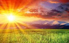Mountains between grass field and sunset
