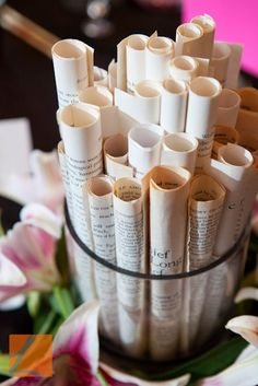 Rolled book pages for table centerpieces. Adding some different height flowers in between might be nice.: