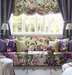 Pinning for curtain length and the idea of such a comfy looking window seat. I need a carpenter! ......This window seat uses both draperies and shades to achieve its glamorous look. Voluminous purple curtains balance out the large floral print of the relaxed Roman shade.